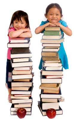Two children resting their arms on tall stacks of books