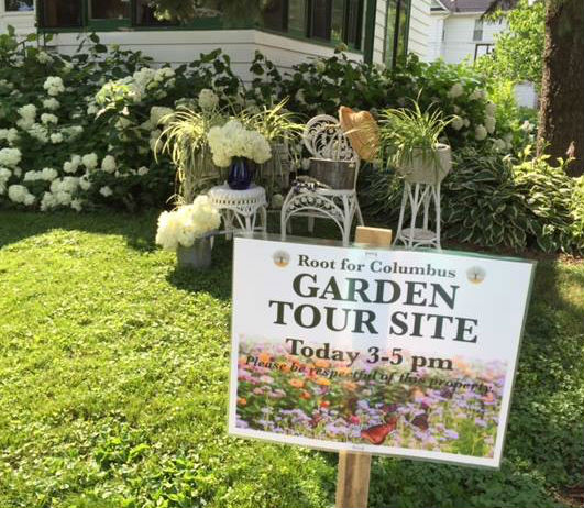 beautiful garden with garden tour sign in yard