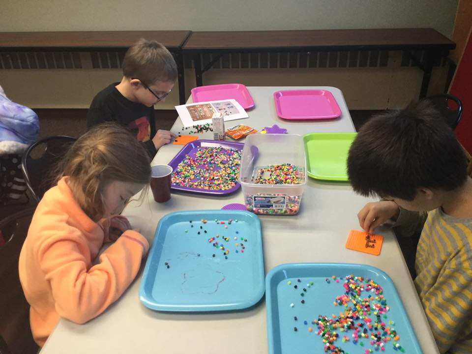 Kids creating Perler Bead art at the library's January 5th Crafternoon.