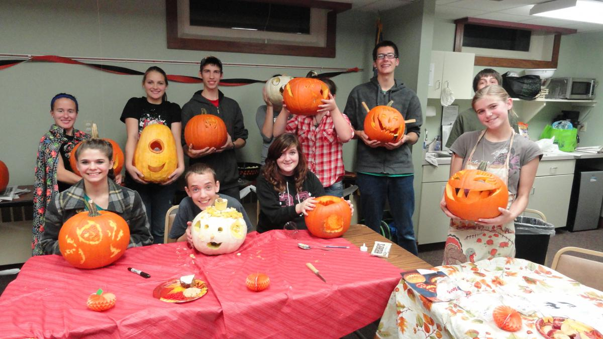 Teens holding their pumpkin carvings