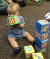 baby holding alphabet blocks