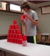 a teen making a large pyramid out of cups
