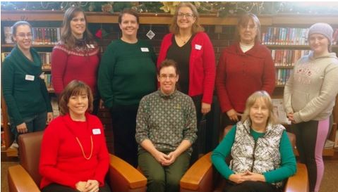 group photo of library staff members standing in front of the fireplace