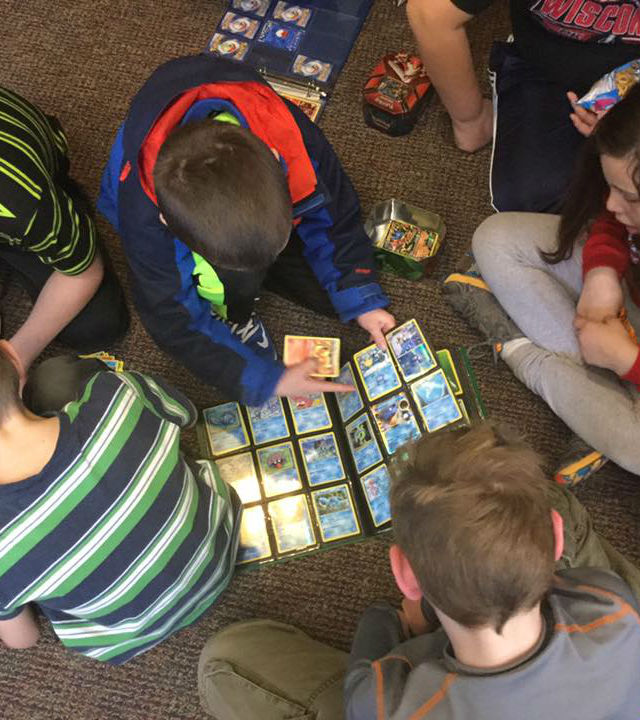 group of children gathered around binder of pokemon cards